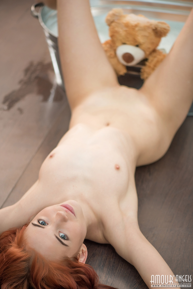 Redhead takes off her dress to pose nude
